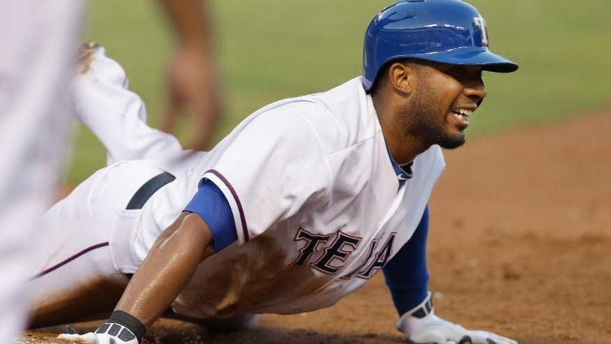 Texas Rangers Elvis Andrus dives back to touch first base beating the pick off throw during the third inning of a baseball game against the Miami Marlins in Arlington, Texas, Tuesday, June 10, 2014. (AP Photo/LM Otero)
