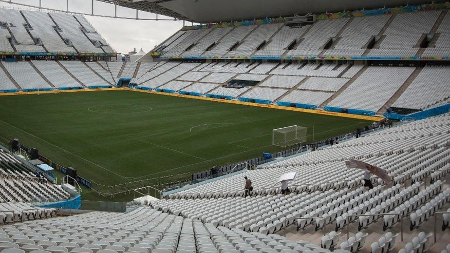 Final preparations are made one day before the opening World Cup soccer match in Itaquerao Stadium in Sao Paulo, Brazil, Wednesday, June 11, 2014. If Brazil wins the opening game, the fact that Itaquerao stadium isn't even fully finished yet will quickly be forgotten. (AP Photo/Felipe Dana)