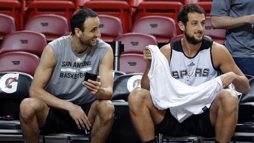 San Antonio Spurs' Manu Ginobili, left, laughs with Marco Belinelli, right, during NBA Finals basketball practice, Wednesday, June 11, 2014, in Miami. The Spurs lead the Miami Heat two games to one, in the best of seven series. (AP Photo/Lynne Sladky)