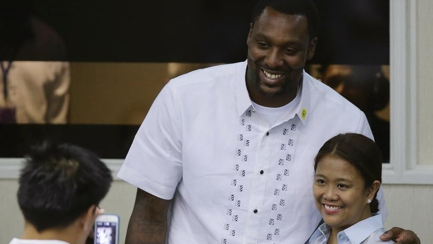 In this Monday, June 9, 2014 photo, American professional basketball player Andray Blatche, center, of the Brooklyn Nets has his picture taken with Philippine senator Nancy Binay during the start of sessions at the Philippine Senate in Pasay city, Philippines. Philippine officials say Blatche has been granted Filipino citizenship today so he could play for the national team in the FIBA World Cup later this year. (AP Photo/Aaron Favila)