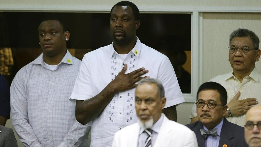 In this photo taken Monday, June 9, 2014, American professional basketball player Andray Blatche, center at back, of the Brooklyn Nets places his hands on his chest as the Philippine national anthem is sung during the start of sessions at the Philippine Senate in Pasay city, Philippines. Philippine officials said Blatche  was granted Filipino citizenship Wednesday so he could play for the national team in the FIBA World Cup later this year. (AP Photo/Aaron Favila)