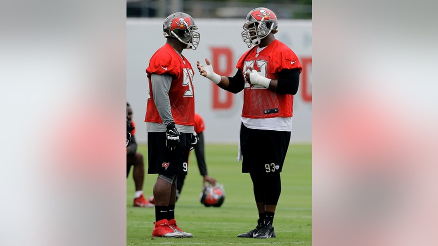 Tampa Bay Buccaneers defensive tackle Gerald McCoy (93) talks to Clinton McDonald (98) during an NFL football minicamp Wednesday, June 11, 2014, in Tampa, Fla. (AP Photo/Chris O'Meara)