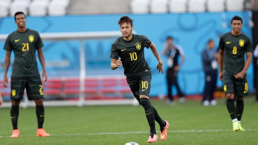 Brazil's Neymar , center, runs for the ball during an official training session the day before the group A World Cup soccer match between Brazil and Croatia in the Itaquerao Stadium, Sao Paulo       , Brazil, Wednesday, June 11, 2014.  (AP Photo/Andre Penner)