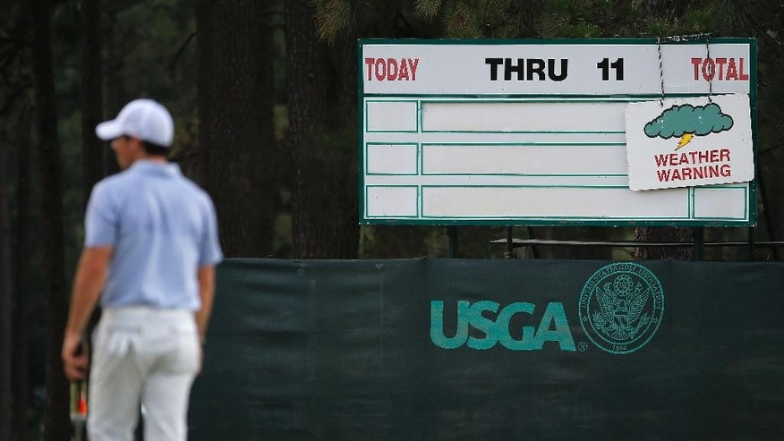 Rory McIlroy, of Northern Ireland, leaves the course after practice was suspended due to weather at the U.S. Open golf tournament in Pinehurst, N.C., Wednesday, June 11, 2014. The tournament starts Thursday. (AP Photo/Matt York)