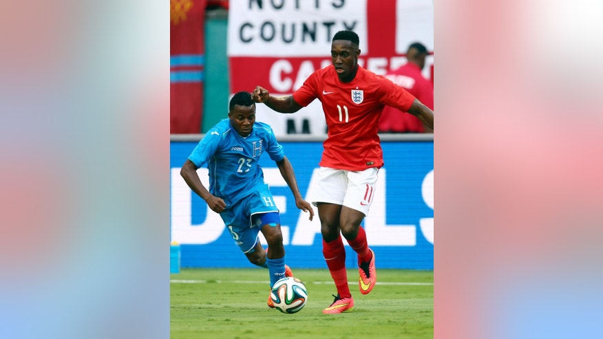 Englands' Danny Welbeck (11) dribbles the ball away from Honduras' Marvin Chavez (23) during the first half of a friendly soccer match in Miami Gardens, Fla., Saturday, June 7, 2014. ( AP Photo/J Pat Carter)