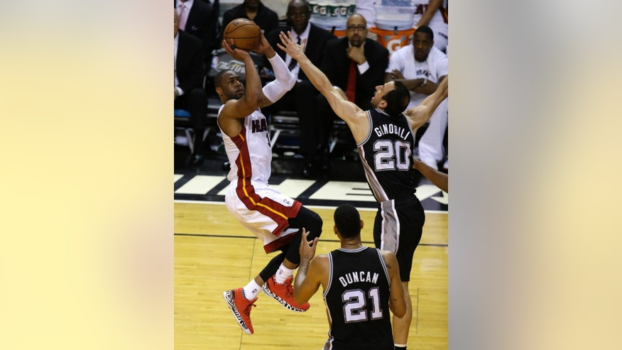 Miami Heat guard Dwyane Wade (3) goes up against San Antonio Spurs guard Manu Ginobili (20) in the second half in Game 3 of the NBA basketball finals, Tuesday, June 10, 2014, in Miami.  (AP Photo/Lynne Sladky)