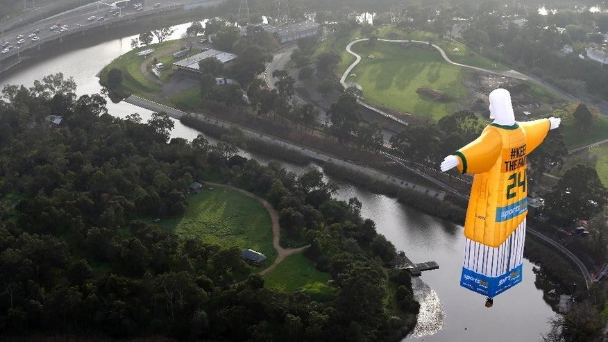 In this photo provided sportsbet.com.au, a hot air balloon in the likeness of Brazil's Christ The Redeemer statute, wearing the colors of Australia's soccer team floats over the Melbourne skyline Tuesday, June 10, 2014. Australia will begin their 2014 soccer World Cup campaign with a match against Chile Saturday, in Cuiaba. (AP Photo/sportsbet.com.au, Dave Callow) EDITORIAL USE ONLY
