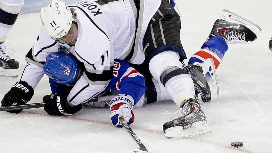 Los Angeles Kings center Anze Kopitar (11) falls to the ice with New York Rangers right wing Jesper Fast (12) in the third period during Game 4 of the NHL hockey Stanley Cup Final, Wednesday, June 11, 2014, in New York. (AP Photo/Frank Franklin II)