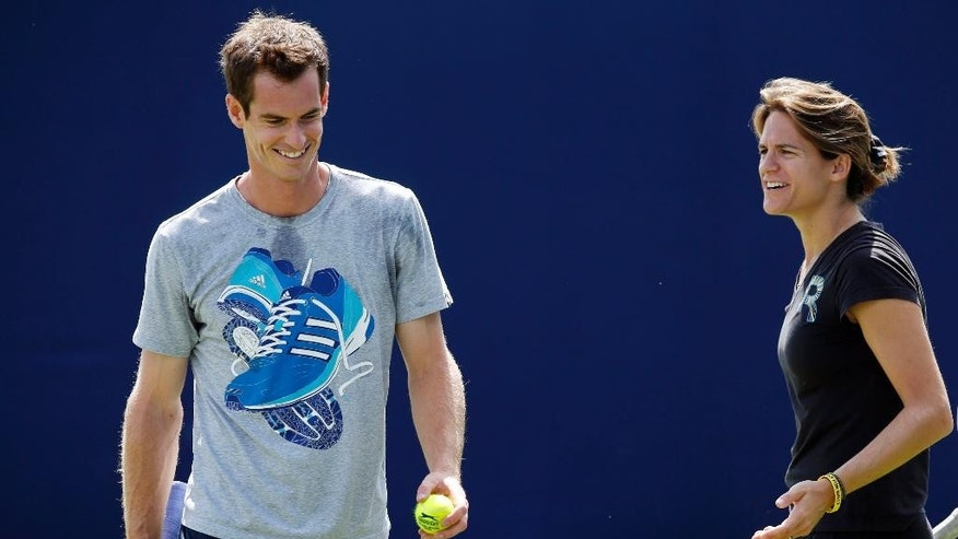 Andy Murray is joined by new coach Amelie Mauresmo, right, at a practice session at The Queen's Club in London, Wednesday June 11, 2014. Murray starts the defence of his title at Queen's Club tournament Wednesday, just hours after beginning with his new coach Mauresmo. (AP Photo / Jonathan Brady, PA) UNITED KINGDOM OUT - NO SALES - NO ARCHIVES