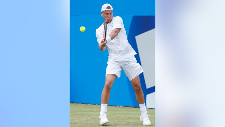 Australia's Lleyton Hewitt  plays a return to Spain's Feliciano Lopez at The Queen's Club, grass-court tournament  in London Wednesday June 11, 2014. Lopez defeat Hewitt  6-3, 6-4.  (AP Photo/Jonathan Brady/PA) UNITED KINGDOM OUT