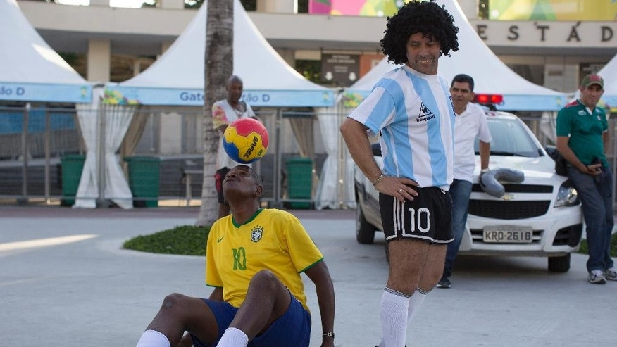 CORRECTING MARADONA ON THE RIGTH - The street performing mime, Daniel Gonzalez, righ, who is dressed to resemble Argentine soccer great Diego Armando Maradona, looks back at Marcio Pereira, dressed up as Brazilian soccer great Pele as he controlls the ball in front of Maracana stadium, Rio de Janeiro, Brazil, Wednesday, June 11, 2014. The World Cup soccer tournament starts Thursday. (AP Photo/Leo Correa)