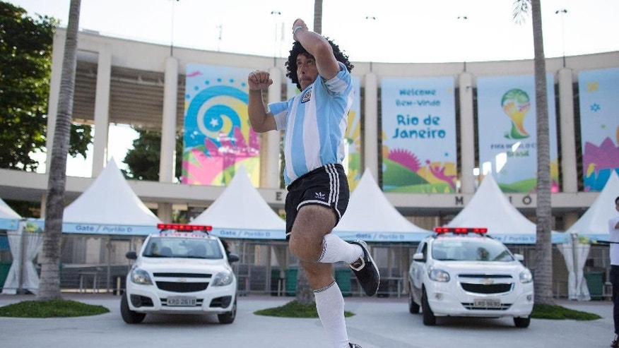 Street performing mime, Daniel Gonzalez, 35, who is dressed to resemble Argentine soccer great Diego Armando Maradona, jumps during his perfromance in front of Maracana stadium, Rio de Janeiro, Brazil, Wednesday, June 11, 2014. The World Cup soccer tournament starts Thursday. (AP Photo/Leo Correa)