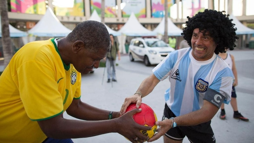 Street performing mime, Daniel Gonzalez, right, who is dressed to resemble Argentine soccer great Diego Armando Maradona, jokes around with the street performer Marcio Pereira, dressed up as former Brazilian soccer great Pele, in front of Maracana stadium, in Rio de Janeiro, Brazil, Wednesday, June 11, 2014. The World Cup soccer tournament starts Thursday. (AP Photo/Leo Correa)