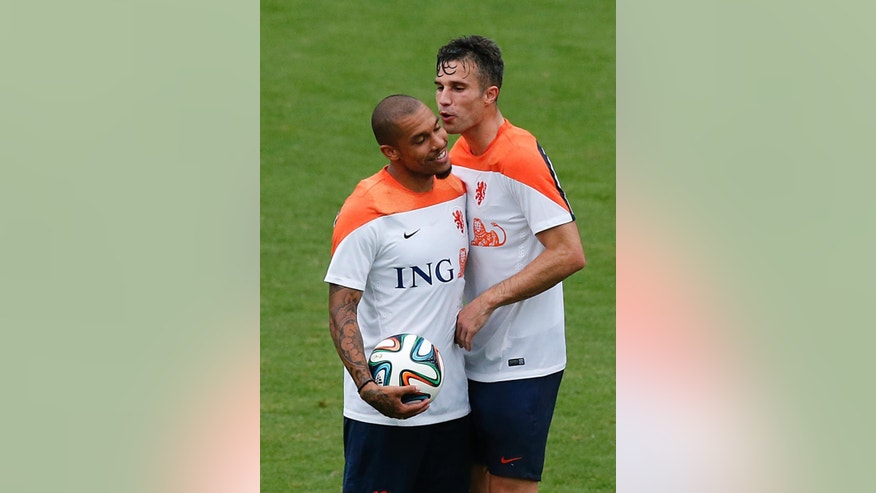 Robin van Persie, right, and Nigel de Jong, left, of the Netherlands share a light moment during a training session in Rio de Janeiro, Brazil, Tuesday, June 10, 2014.  The Netherlands play in group B of the 2014 soccer World Cup. (AP Photo/Wong Maye-E)