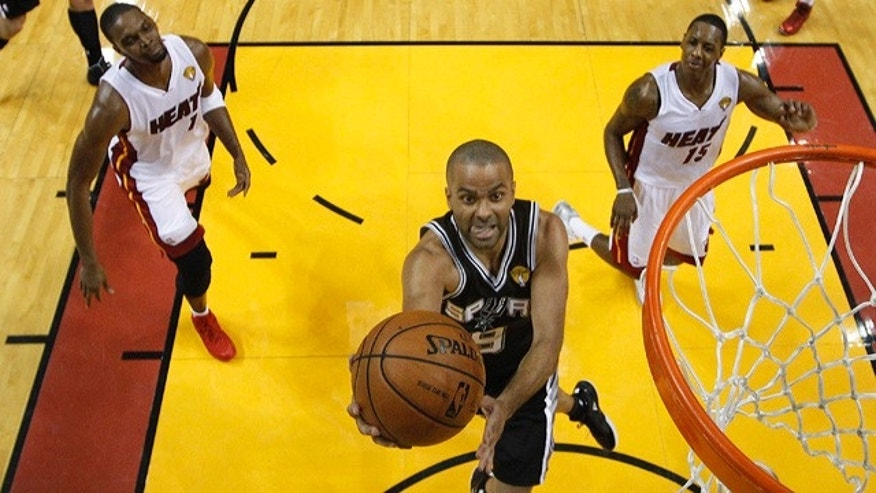 June 10, 2014: San Antonio Spurs guard Tony Parker (9) drives to the basket over Miami Heat center Chris Bosh (1) and guard Mario Chalmers (15),  during the first half of Game 3 of the NBA Finals in Miami. (AP Photo/Wilfredo Lee)