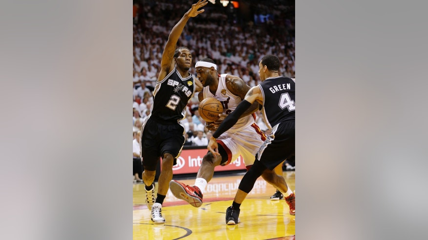 San Antonio Spurs forward Kawhi Leonard (2) and guard Danny Green (4) defend Miami Heat forward LeBron James (6), during the first half in Game 3 of the NBA basketball finals, Tuesday, June 10, 2014, in Miami. (AP Photo/Wilfredo Lee)