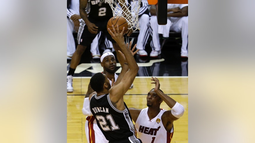 San Antonio Spurs forward Tim Duncan (21) prepares to shoot as Miami Heat center Chris Bosh (1) and LeBron James defend in the first half in Game 3 of the NBA basketball finals, Tuesday, June10, 2014, in Miami.  (AP Photo/Lynne Sladky)