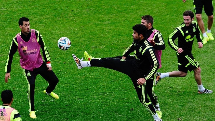Spain's Diego Costa, second left, and Sergio Busquets, left, duel for the ball during a training session at he Atletico Paranaense training center in Curitiba, Brazil, Tuesday, June 10, 2014. Spain will play in group B of the Brazil 2014 World Cup. (AP Photo/Manu Fernandez)
