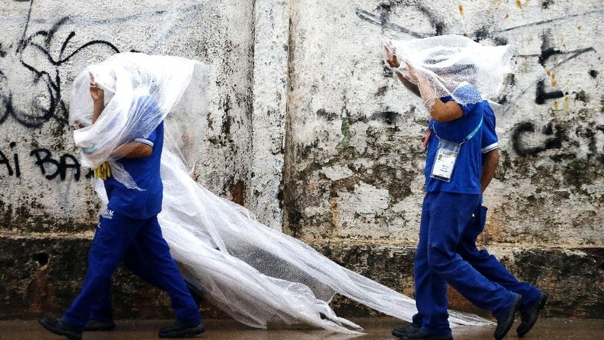 Workers cover themselves from the rain with a plastic as they leave a 2014 soccer World Cup venue, the Arena da Amazonia in Manaus, Brazil, Wednesday, June 11, 2014. The 2014 World Cup is set to begin Thursday, with Brazil and Croatia competing in the opening match in Sao Paulo. (AP Photo/Themba Hadebe)