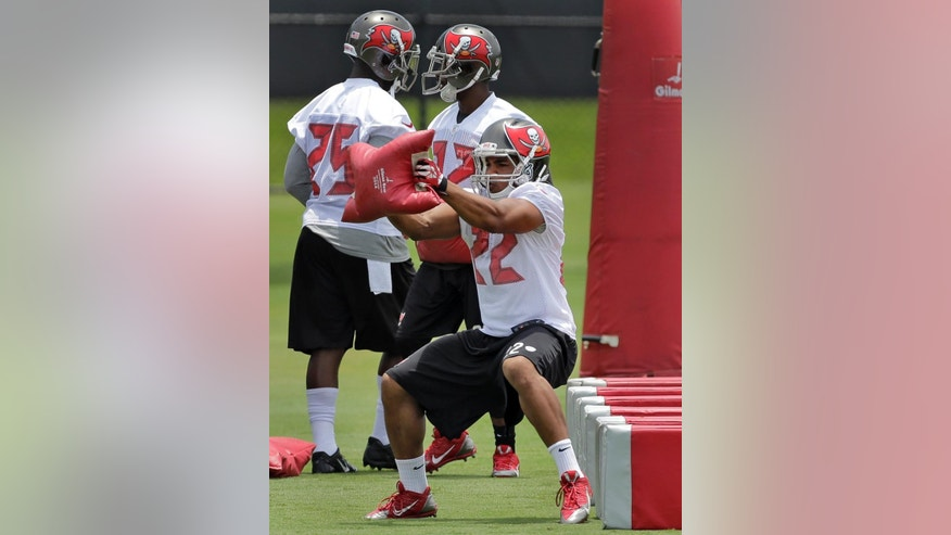 Tampa Bay Buccaneers running back Doug Martin carries a sand bag as he runs through drills during an NFL football minicamp Thursday, June 12, 2014, in Tampa, Fla. (AP Photo/Chris O'Meara)