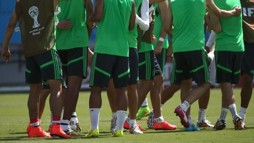 Mexico's soccer players warm up during a training session for the World Cup in the Arena das Dunas stadium in Natal, Brazil, Thursday, June 12, 2014.  (AP Photo/Sergei Grits)