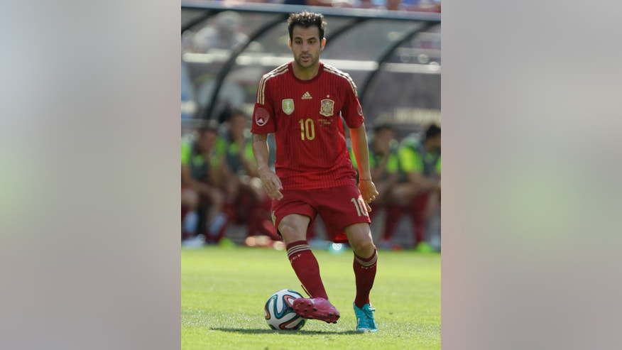 In this June 7, 2014 photo, Spain's Cesc Fabregas wears his new  Puma cleats during the first half of an exhibition soccer game against El Salvador, in Landover, Md. Nike, Adidas and Puma are all trotting out new looks and innovation in footwear for this summer's World Cup. The result will be a clash of colors when the teams take the field in Brazil.  (AP Photo/Luis M. Alvarez)