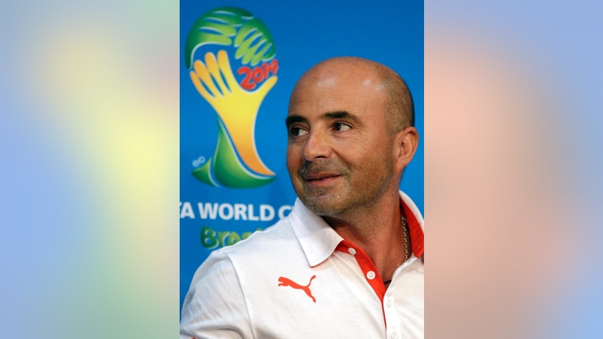 Chile's head coach Jorge Sampaoli stands in front of a World Cup logo as he leaves after a press conference the day before the group B World Cup soccer match between Chile and Australia in the Arena Pantanal in Cuiaba, Brazil, Thursday, June 12, 2014. (AP Photo/Michael Sohn)
