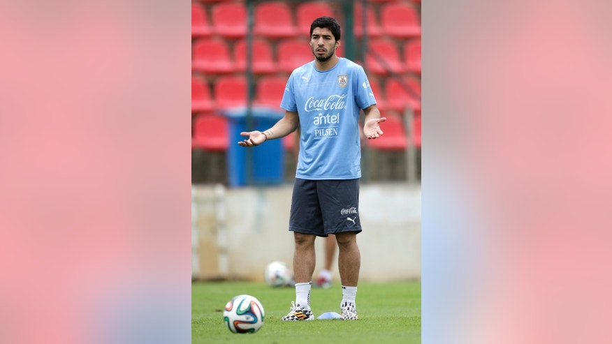 Luis Suarez joins his team's practice session at Arena do Jacare Stadium before the start of the World Cup soccer tournament in Sete Lagoas, Brazil, Thursday, June 12, 2014.  (AP Photo/Bruno Magalhaes)