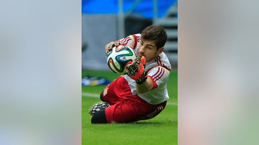 Spain's goalkeeper Iker Casillas stops the ball during an official training session the day before the group B World Cup soccer match between Spain and the Netherlands at the Arena Ponte Nova in Salvador, Brazil, Thursday, June 12, 2014.  (AP Photo/Bernat Armangue)