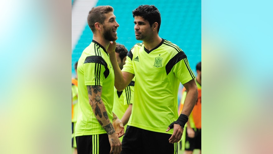 Spain's Diego Costa jokes with teammate Sergio Ramos during an official training session the day before the group B World Cup soccer match between Spain and the Netherlands at the Arena Ponte Nova in Salvador, Brazil, Thursday, June 12, 2014.  (AP Photo/Manu Fernandez)
