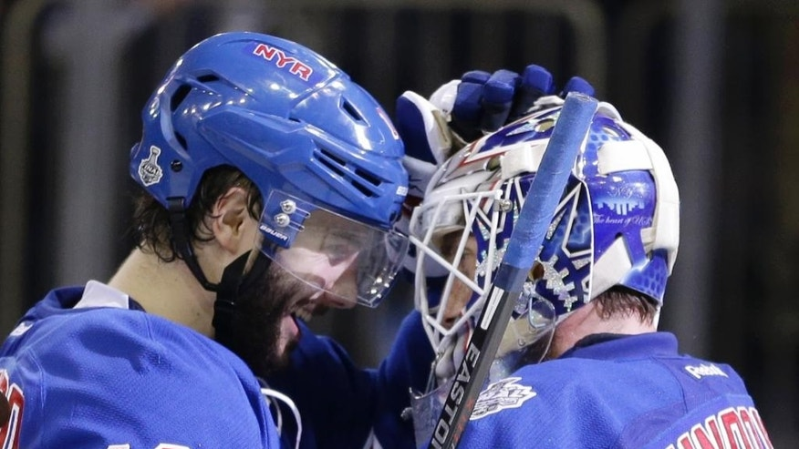 New York Rangers center Derick Brassard (16) congratulates goalie Henrik Lundqvist (30) after the Rangers beat the Los Angeles Kings 2-1 in Game 4 of the NHL hockey Stanley Cup Final, Wednesday, June 11, 2014, in New York. (AP Photo/Seth Wenig)