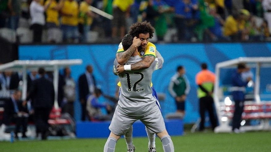 Brazil's Marcelo celebrates with  goalkeeper Julio Cesar after Oscar scored the 3rd goal during the group A World Cup soccer match between Brazil and Croatia, the opening game of the tournament, in the Itaquerao Stadium in Sao Paulo, Brazil, Thursday, June 12, 2014.  (AP Photo/Felipe Dana)