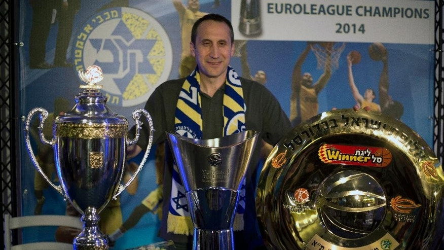 "Maccabi Tel Aviv's head coach David Blatt poses for photographers with the Israeli cup, European club champions cup and the Israeli club champions trophy after a news conference in Tel Aviv, Israel,Thursday, June 12, 2014. David Blatt has stepped down as coach of European club champion Maccabi Tel Aviv to pursue a job in the NBA. Blatt told a news conference on Thursday he wanted to fulfil his ""dream"" of coaching in the NBA. He says he is weighing offers from unnamed teams. The Cleveland Cavaliers, Minnesota Timberwolves and Golden State Warriors are all believed to be interested. Blatt, who grew up near Boston and played college ball at Princeton, has had a successful career coaching overseas. Last month, he led Maccabi to an upset win over Real Madrid in the European basketball championship. At a championship celebration, Prime Minister Benjamin Netanyahu playfully told Blatt not to leave. (AP Photo/Ariel Schalit)"