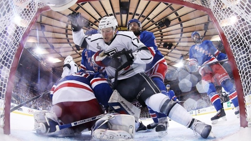 June 11, 2014: New York Rangers defenseman Dan Girardi (5) grabs Los Angeles Kings center Tyler Toffoli (73) as he falls toward the net in the third period of Game 4 of the Stanley Cup Final. (AP Photo/Bruce Bennett, Pool)