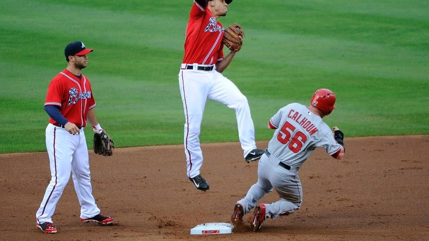 Atlanta Braves shortstop Andrelton Simmons, center, forces out Los Angeles Angels' Kole Calhoun (56) at second base as Braves' Tommy La Strella backs him up during the first inning of a baseball game on Friday, June 13, 2014, in Atlanta. (AP Photo/David Tulis)