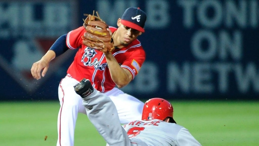 Los Angeles Angels' David Freese (6) is caught stealing by Atlanta Braves shortstop Andrelton Simmons, top, during the fourth inning of a baseball game on Friday, June 13, 2014, in Atlanta. (AP Photo/David Tulis)