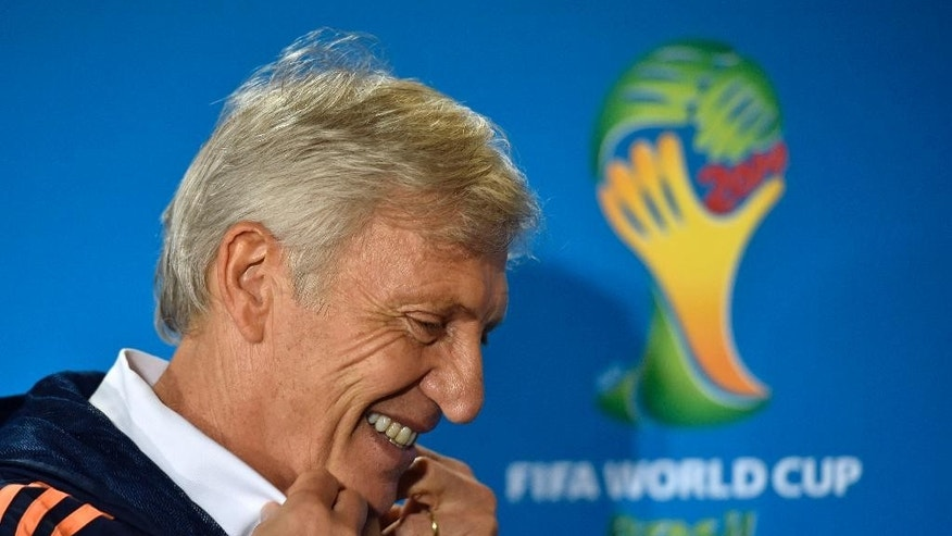 Colombia's head coach Jose Pekerman leaves a press conference smiling on the day before the group C World Cup soccer match between Colombia and Greece at the Mineirao Stadium in Belo Horizonte, Brazil, Friday, June 13, 2014.  (AP Photo/Martin Meissner)
