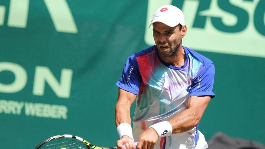 Colombia's Alejandro Falla returns the ball against Germany's Peter Gojowczyk quarterfinal match at the Gerry Weber Open tennis tournament in  Halle, Germany, Friday, June 13, 2014. Falla won the match with 7-6 and 7-6. (AP Photo/dpa, Oliver Krato)