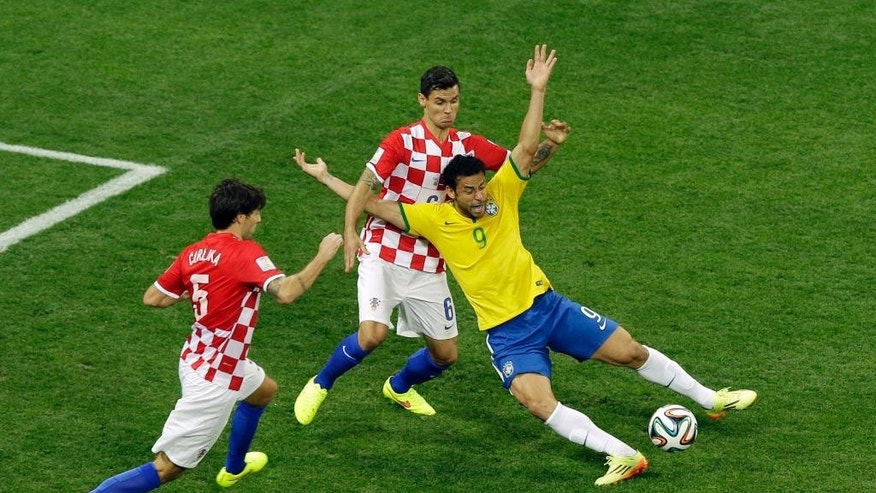 Brazil's Fred, right, falls after making contact with Croatia's Dejan Lovren during the group A World Cup soccer match between Brazil and Croatia, the opening game of the tournament, in the Itaquerao Stadium in Sao Paulo, Brazil, Thursday, June 12, 2014. At left is Croatia's Vedran Corluka. (AP Photo/Thanassis Stavrakis)