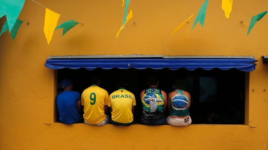 Brazilian residents watch the opening match of the FIFA World Cup between Brazil and Croatia in Porto Seguro, Brazil, Thursday, June 12, 2014. (AP Photo/Matthias Schrader)