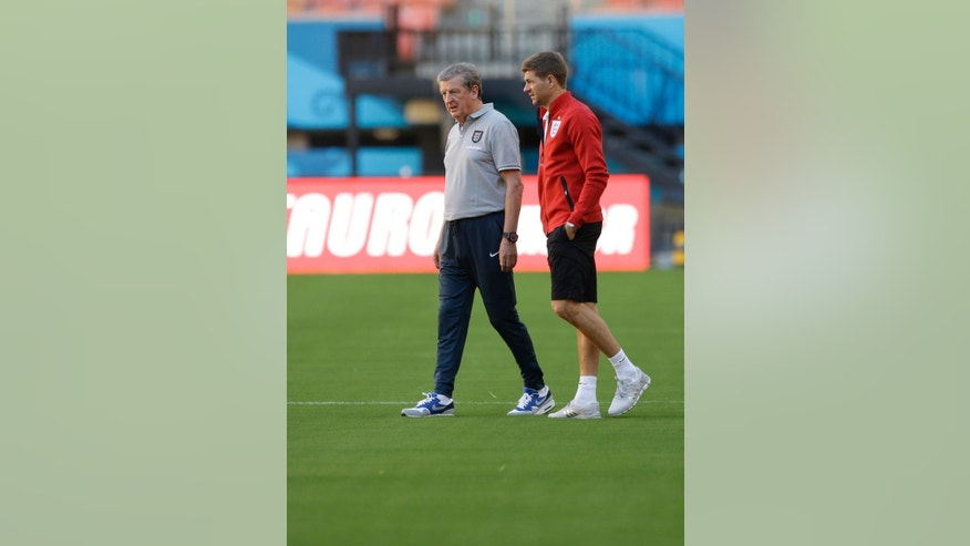 England's manager Roy Hodgson, left, and captain Steven Gerrard look at the condition of the pitch at the start of a training session of the England national soccer team at the Arena da Amazonia in Manaus, Brazil, Friday, June 13, 2014.  England play Italy in group D of the 2014 soccer World Cup at the stadium on Saturday.  (AP Photo/Matt Dunham)