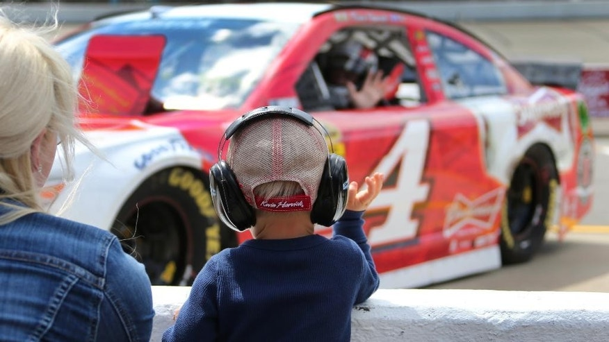 Keelan Harvick waves to his father Kevin Harvick before the qualifying session for Sunday's NASCAR Sprint Cup series Quicken Loans 400 auto race at Michigan International Speedway in Brooklyn, Mich., Friday, June 13, 2014. (AP Photo/Bob Brodbeck)