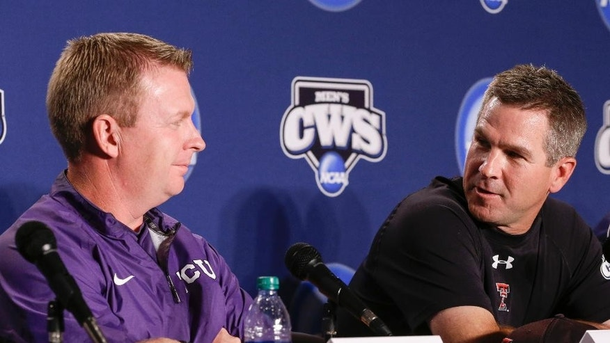 TCU coach Jim Schlossnagle, left, and Texas Tech coach Tim Tadlock exchange glances during a coaches news conference held Friday, June 13, 2014, ahead of the NCAA baseball College World Series tournament at TD Ameritrade Park in Omaha, Neb. Texas Tech plays TCU on Sunday. (AP Photo/Nati Harnik)