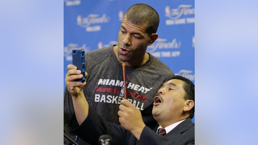 "File- This June 4, 2014, file photo shows Miami Heat forward Shane Battier singing with a late show personality Guillermo Rodriguez after basketball practice  in San Antonio. ""International growth and expansion is the obvious outlet for our game,"" Battier said. ""I think that domestically, we've tapped pretty much every pigeonhole and foxhole we can find. Because the game is so popular globally, it's only a matter of time before we take our game in person to our fans around the world. The logistics argument is always the argument that detractors want to bring up, but it's inevitable."" (AP Photo/Eric Gay, File)"