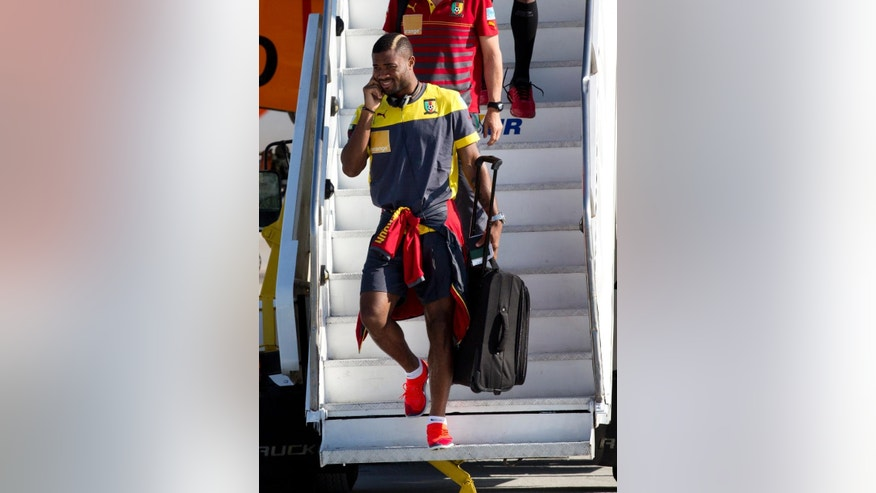 FC Barcelona's player Alex Song descends the stairs of the aircraft  as Cameroon's national team arrives at the Galeao Air Base in Rio de Janeiro, Brazil, Monday, June 9, 2014. Cameroon's World Cup team refused to board a plane due to take them to Brazil on Sunday because of a long-running dispute over bonus payments for the tournament, forcing their national federation to take out a loan to meet their demands. (AP Photo/Rodrigo Abd)