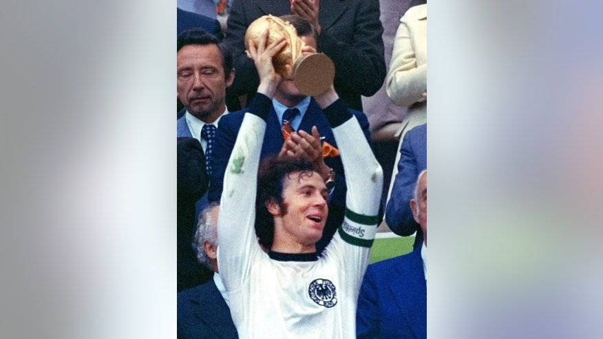 FILE - The July 7, 1974 file photo shows then captain of the German national soccer team Franz Beckenbauer raising the trophy after Germany won the World Cup final in Munich, southern Germany. Beckenbauer has been banned from football duty for 90 days for snubbing an investigation into Qatar's 2022 World Cup bid. FIFA said Friday, June 13, 2014 the 90-day provisional ban was requested by ethics prosecutor Michael Garcia. Beckenbauer was a voting member of FIFA's executive committee in December 2010 when it chose Qatar, and Russia as 2018 World Cup host. (AP Photo/file)