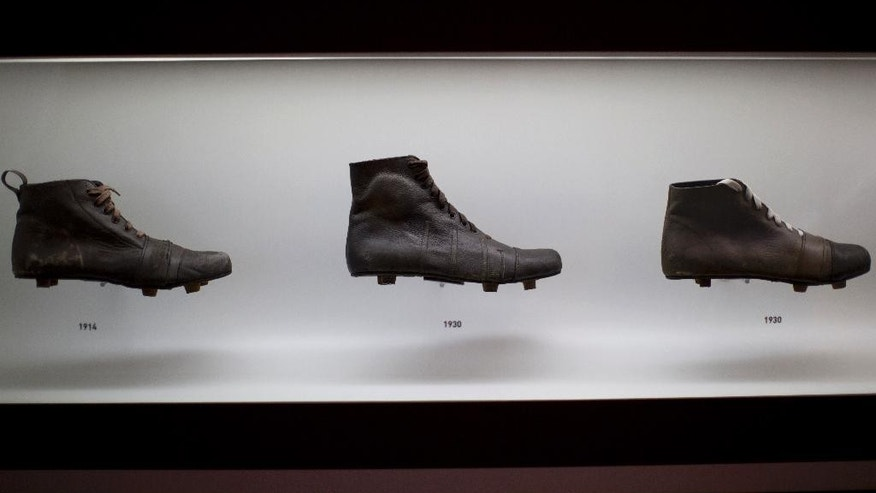 In this June 12, 2014 photo, soccer cleats from 1914, left, and 1930 are displayed at the Soccer Museum in Sao Paulo, Brazil. The museum dedicates ample space to explain the importance of Charles Miller, an English-educated Brazilian who brought soccer to Brazil from England, and is celebrated in Brazil as the forefather of Brazilian soccer. (AP Photo/Dario Lopez-Mills)