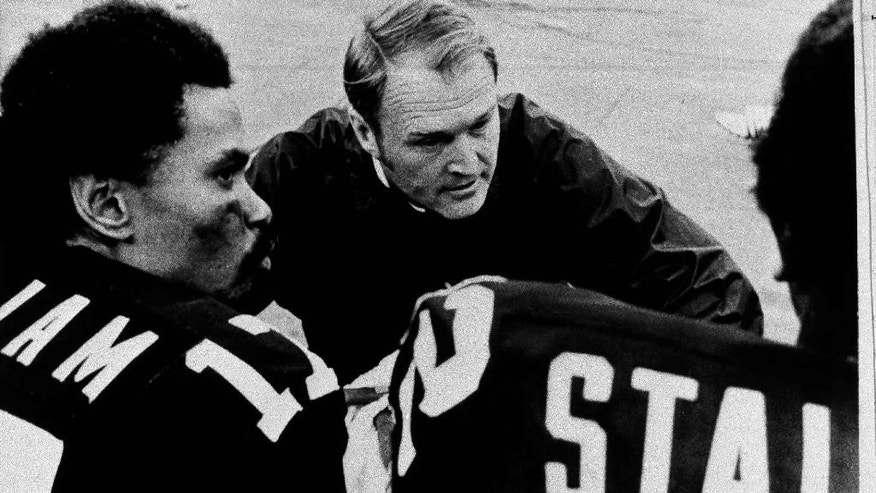 File-This Sept. 29, 1975, file photo shows Pittsburgh Steelers coach Chuck Noll conferring with quarterback Joe Gilliam, left, and wide receiver John Stallworth during game in Pittsburgh, Pa. Noll, the Hall of Fame coach who won a record four Super Bowl titles with the Pittsburgh Steelers, died Friday, June 13, at his home. He was 82. The Allegheny County Medical Examiner said Noll died of natural causes. (AP Photo/File)