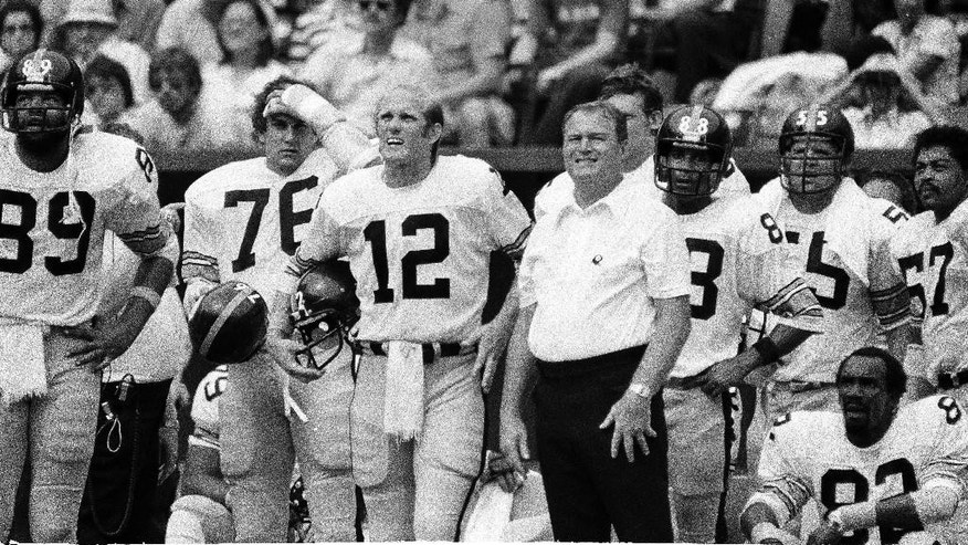 File- This Sept. 18, 1978, file photo shows Pittsburgh Steelers coach Chuck Noll smiling as he and quarterback Terry Bradshaw watch  the defense play against the Bengals in Cincinnati, Ohio. Noll, the Hall of Fame coach who won a record four Super Bowl titles with the Pittsburgh Steelers, died Friday, June 13, 2014, at his home. He was 82. The Allegheny County Medical Examiner said Noll died of natural causes. (AP Photo/File)