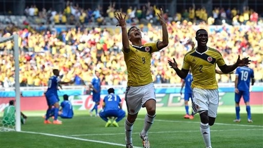 Colombia's Teofilo Gutierrez (9) celebrates with his teammate Cristian Zapata after scoring his side's second goal during the group C World Cup soccer match between Colombia and Greece at the Mineirao Stadium in Belo Horizonte, Brazil, Saturday, June 14, 2014. (AP Photo/Martin Meissner)